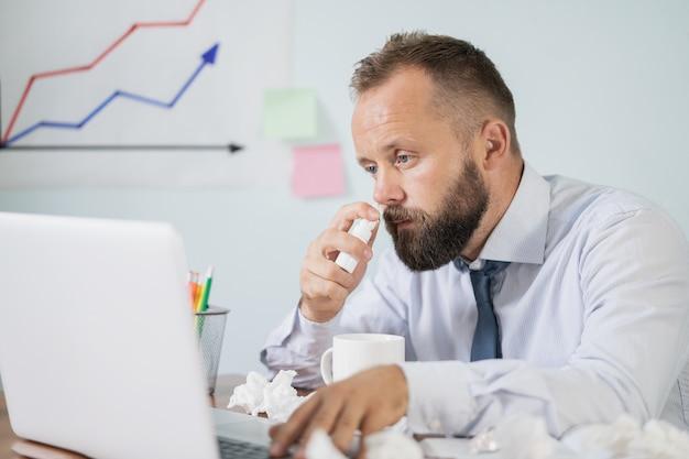 Enfermo en el trabajo, un hombre joven tiene alergia a la gripe, estornudos, soplar, limpiar, correr la nariz en el tejido