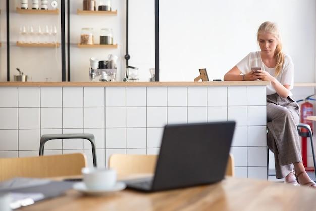 Enfocada hermosa mujer rubia con smartphone, sentada en la encimera de la cocina en el espacio de trabajo conjunto