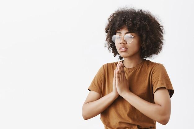 Enfocada relajada y tranquila atractiva joven mujer de piel oscura con gafas con peinado afro de pie medio girado hacia la izquierda con los ojos cerrados gesto namaste o manos en oración meditando