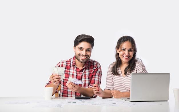 Enfocado en la contabilidad de la joven pareja india, calcular facturas, discutir la planificación del presupuesto juntos utilizando servicios bancarios en línea y calculadora, verificar las finanzas