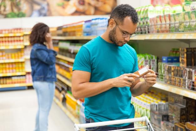 Enfocado hombre afroamericano leyendo información sobre envases