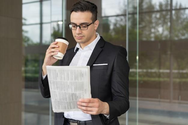 Enfocado joven inversor mirando a través de las últimas noticias financieras