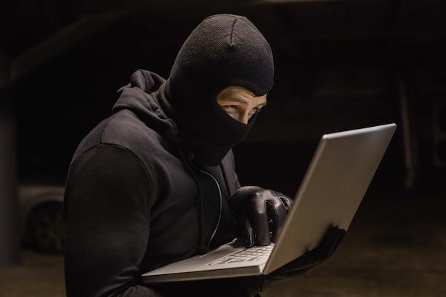 Enfocado ladrón de pie con portátil
