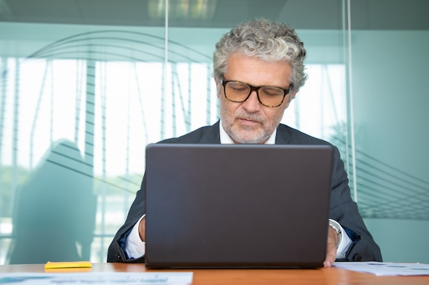 Enfocado profesional maduro vistiendo traje y gafas, trabajando en equipo en la oficina, usando el portátil en la mesa
