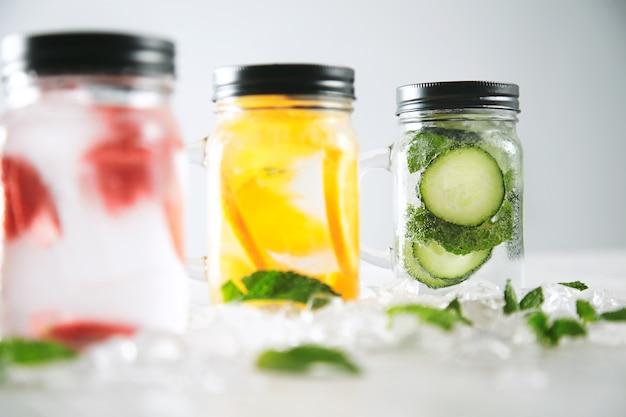 Enfoque de cerca en el último tarro limonadas caseras frescas saludables con agua con gas fresa, pepino, menta y naranja aislados en cubitos de hielo rotos en la mesa de madera