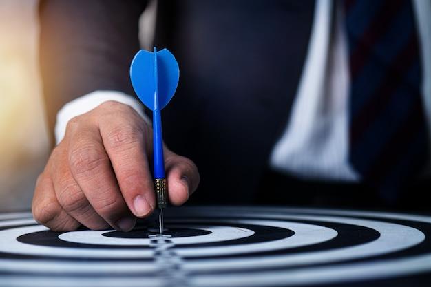 Enfoque de empresario para apuntar lanzando dardos en la focalización