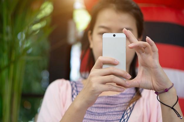 Enfoque la mano de la mujer asiática joven que toca el teléfono inteligente