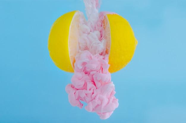 Enfoque parcial de disolver el color rosado del cartel en la gota de agua entre limones sobre fondo azul