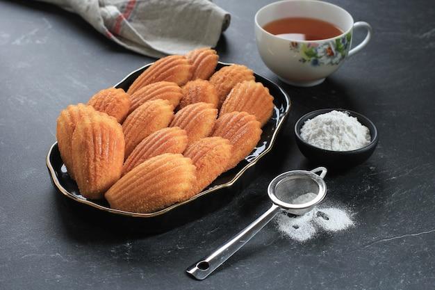 Enfoque seleccionado madeleine de vainilla sobre plato de cerámica negra. famoso pastel de concha dulce francés con azúcar espolvoreado, servido con té