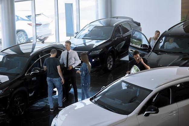 Enfoque selectivo de un agente de ventas que habla con los clientes en un concesionario de automóviles