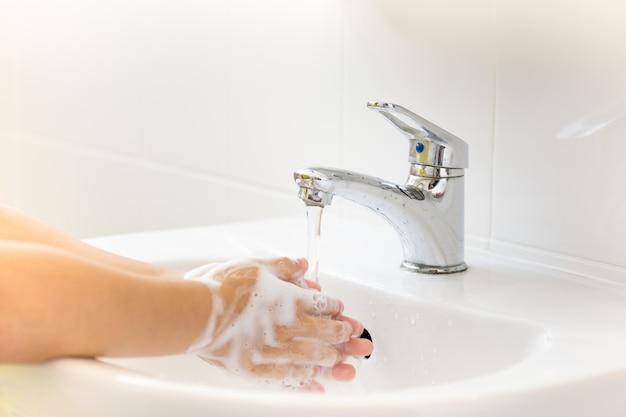 Enfoque selectivo del agua del grifo los niños se lavan las manos con jabón bajo el grifo del baño.