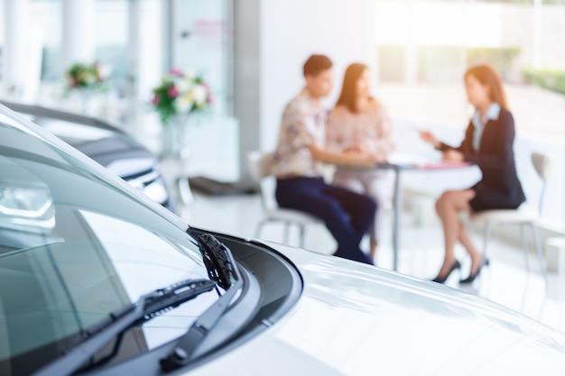 Enfoque selectivo en un auto nuevo y difuminar al vendedor profesional del concesionario y a la pareja que compra un auto nuevo. concepto profesionalismo acuerdo contrato arrendamiento arrendamiento alquiler venta minorista.