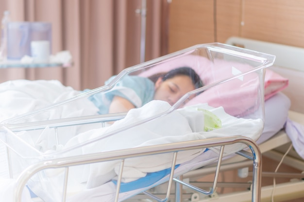 Enfoque selectivo del bebé recién nacido y la nueva madre durmiendo en un hospital