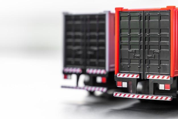 Enfoque selectivo de camiones de contenedores sobre fondo blanco, estacionamiento de camiones de contenedores de remolque en el almacén, empresa de transporte de transporte y logística comercial global.