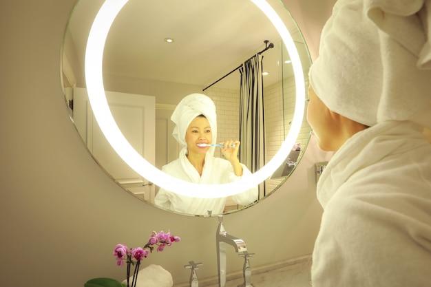 Enfoque selectivo en la cara, retrato de hermosa mujer asiática en bata de baño y con una toalla sobre su cabeza limpiando sus dientes en el baño.
