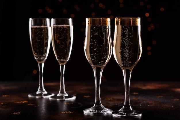 Enfoque selectivo de copas llenas de champán contra las luces de navidad