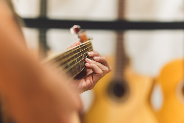 Enfoque selectivo en las cuerdas de una guitarra clásica mientras es tocada por una mujer.