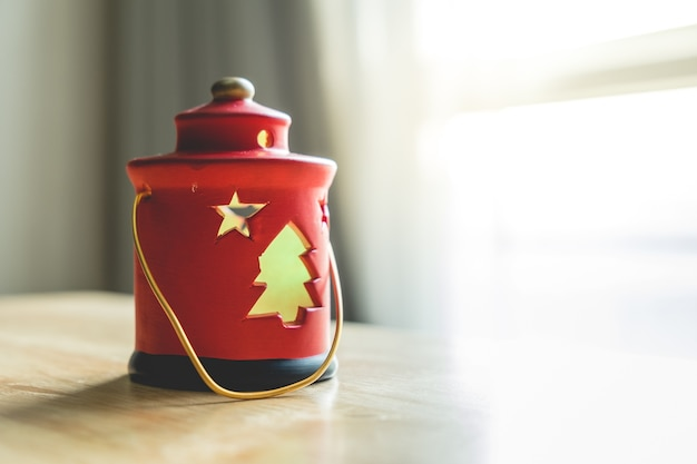 Enfoque selectivo con la decoración de la lámpara roja de navidad en la mesa de madera