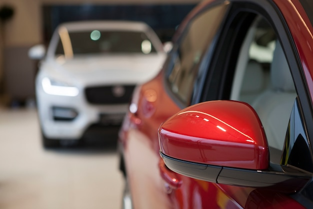 El enfoque selectivo en el espejo lateral de un nuevo automóvil rojo en el concesionario, espacio de copia