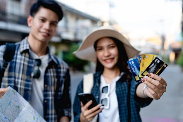 Enfoque selectivo, joven mochilero sosteniendo un mapa de papel y una mujer bonita con sombrero sostiene un teléfono inteligente y muestra una tarjeta de crédito en la mano.los usan para pagar el viaje con felicidad en vacaciones.