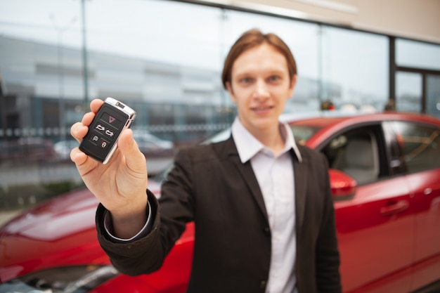 El enfoque selectivo en la llave del coche en la mano de un joven alegre en el concesionario