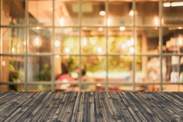 Enfoque selectivo de mesa de madera delante de luces decorativas de cadena interior.