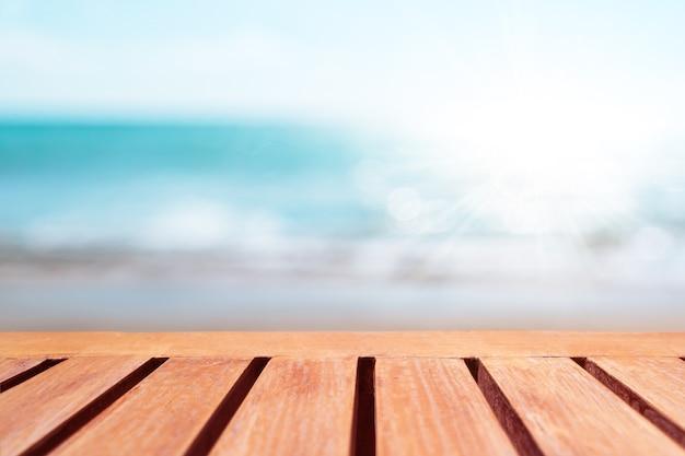 Enfoque selectivo de la mesa de madera vieja con un hermoso fondo de playa para mostrar su producto.