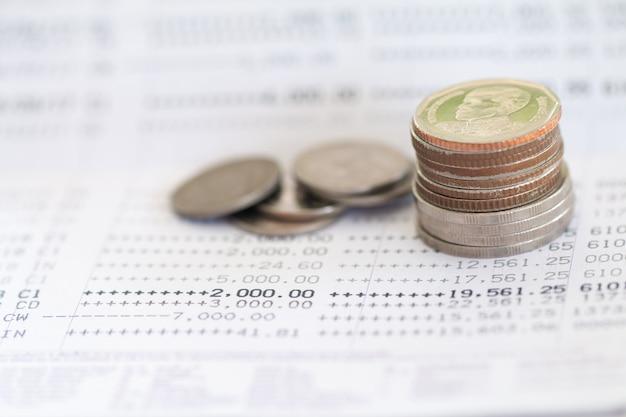 Enfoque selectivo de las monedas de tailandia apiladas en la página del extracto de la cuenta bancaria.