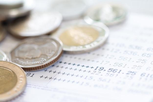 Enfoque selectivo de las monedas de tailandia apiladas sobre la página del extracto de la cuenta bancaria sobre fondo blanco.