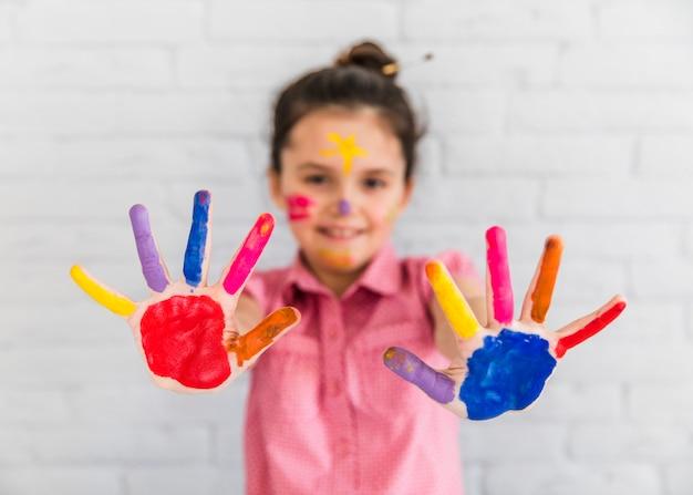 Enfoque selectivo de una niña mostrando manos pintadas de colores.