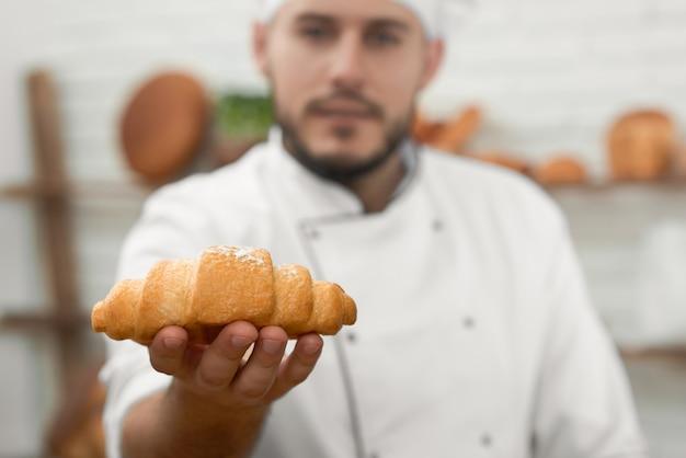 El enfoque selectivo en un panadero profesional de croissant fresco y sabroso está sosteniendo el concepto de panadería de la tienda de la tienda de descuento de la oferta de venta de alimentos de la ocupación de la profesión de copyspace.