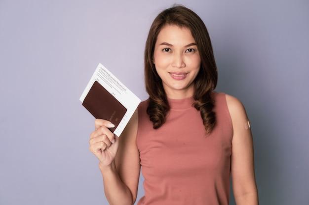 Enfoque selectivo en el pasaporte, mujer asiática vacunada sosteniendo y mostrando la tarjeta de registro de inyección de la vacuna y el pasaporte en concepto de listo para viajar después de la vacunación covid-19 y finalizar el brote del virus.