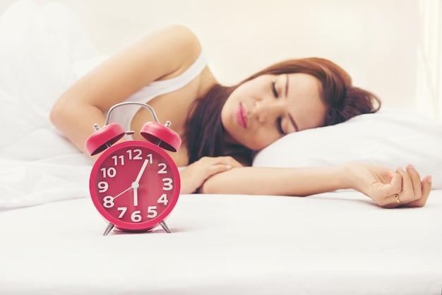 Enfoque selectivo reloj de alarma roja en frente de la niña duerme en la cama.