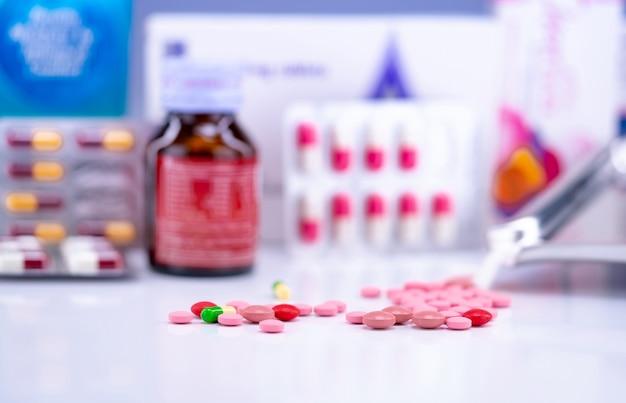 Enfoque selectivo en tabletas y píldoras cápsulas en el fondo borroso de la botella de droga, blister de píldoras y bandeja de drogas. productos de farmacia.
