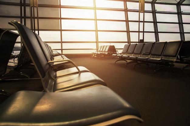 Enfoque suave del asiento vacío en la terminal de salidas del aeropuerto en la mañana temprano