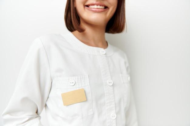 Enfoque suave en la placa en blanco con espacio para texto en la bata blanca del médico con una hermosa sonrisa. retrato recortado con espacio de copia.