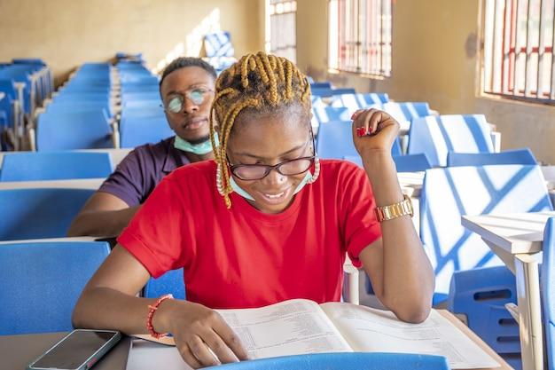 Enfoque superficial de dos estudiantes con mascarillas y estudiando en un aula