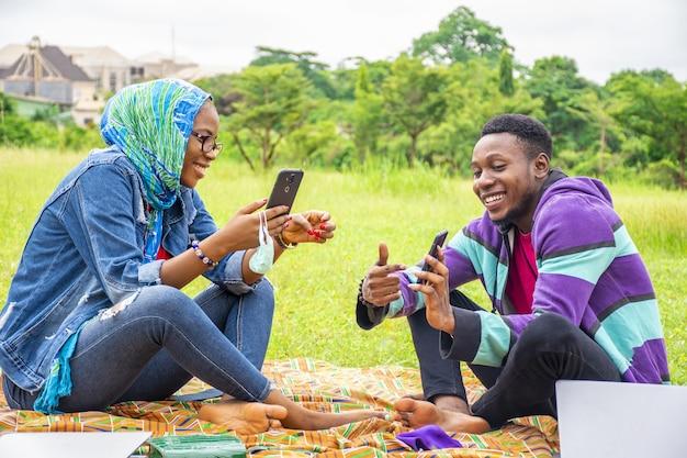 Enfoque superficial de dos jóvenes amigos pasando el rato en un parque mientras usan sus teléfonos