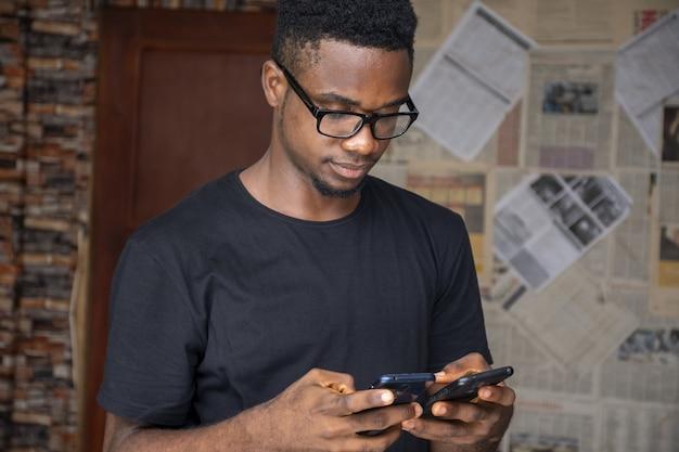 Enfoque superficial de un hombre joven con gafas usando dos teléfonos en una habitación