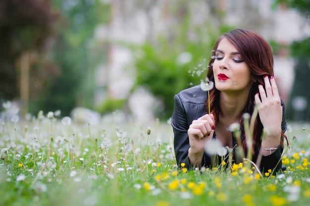 Enfoque superficial de una joven elegante tumbado en un parque y soplando un diente de león