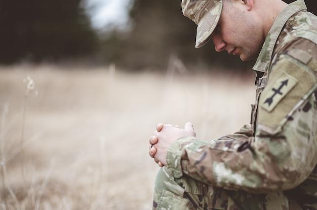 Enfoque superficial de un joven soldado rezando mientras está de rodillas sobre una hierba seca