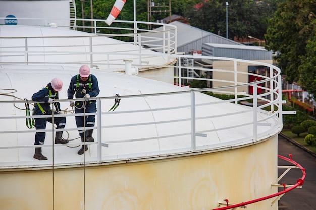 Enfoque trabajador masculino acceso por cuerda inspección de seguridad de altura del tanque de aceite y gas de almacenamiento de espesor