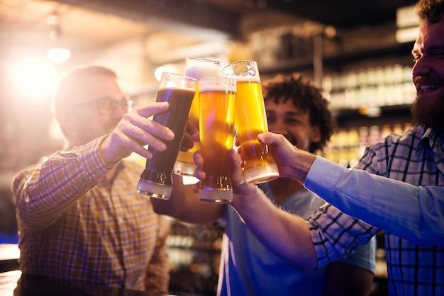 Enfoque la vista de manos y vasos de cerveza mientras felices amigos multiculturales casuales tintinean vasos de cerveza en el pub.