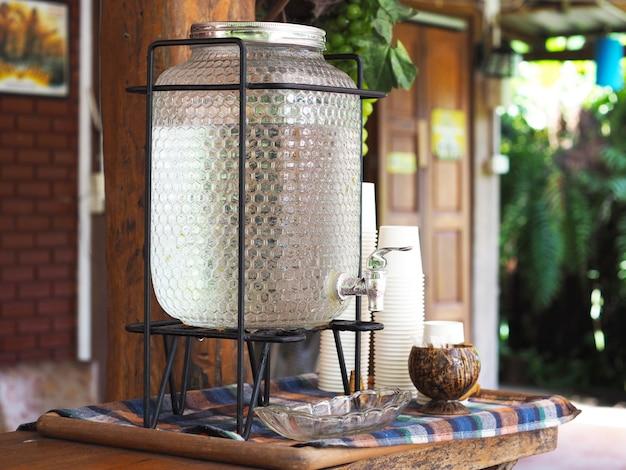 Enfriador de agua de vidrio vintage y taza de papel blanco