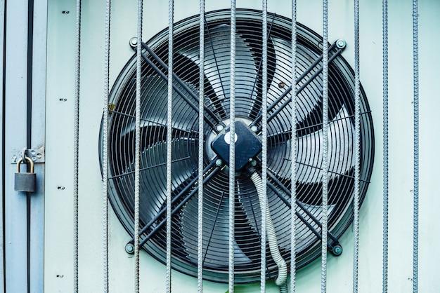 El enfriador de aire acondicionado industrial al aire libre detrás de la cerca está bloqueado en un candado con espacio de copia.