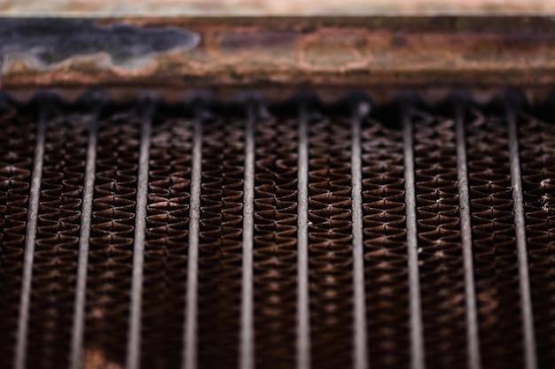 Enfriador automotriz viejo y oxidado. textura de celosía roja oxidada. cuadrícula.