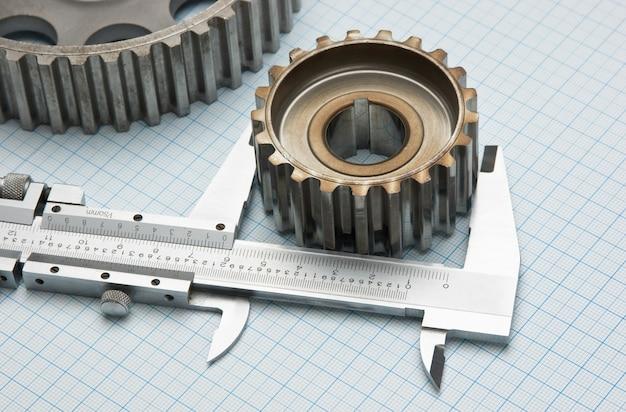 Engranajes y pinza sobre papel cuadriculado