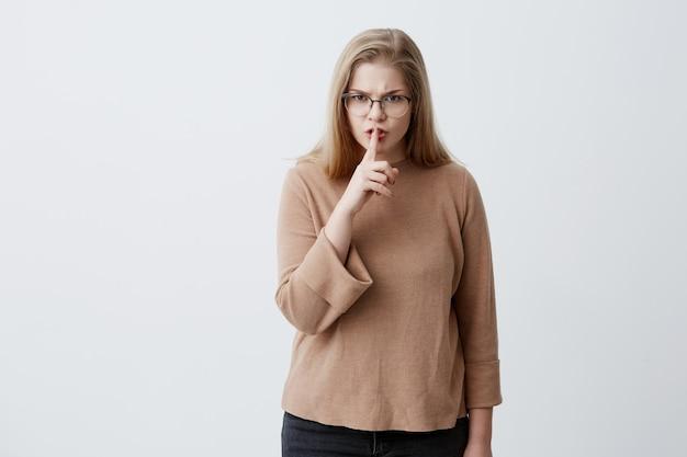 Enojada, molesta, vestida de manera informal, mujer rubia con gafas manteniendo el dedo índice en los labios, diciendo shh, pidiendo silencio y privacidad, irritada con música o ruido. emociones y sentimientos negativos