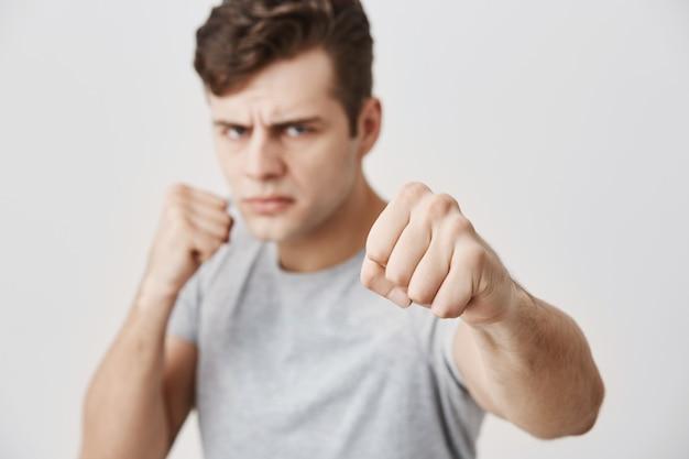 Enojado agresivo joven varón caucásico de pie en posición defensiva, manteniendo los puños cerrados, con una mirada segura y autodeterminada, listo para defenderse y defender sus derechos