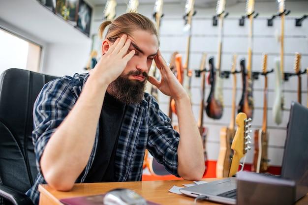 Enojado y cansado joven inconformista sentarse a la mesa en la sala. se toma las manos cerca de la cabeza. guy tiene dolor de cabeza. muchas guitarras eléctricas colgando detrás de él.